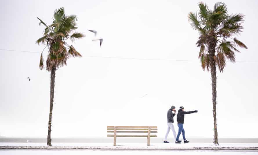 People walk along the snow-covered promenade in Southend, Essex.