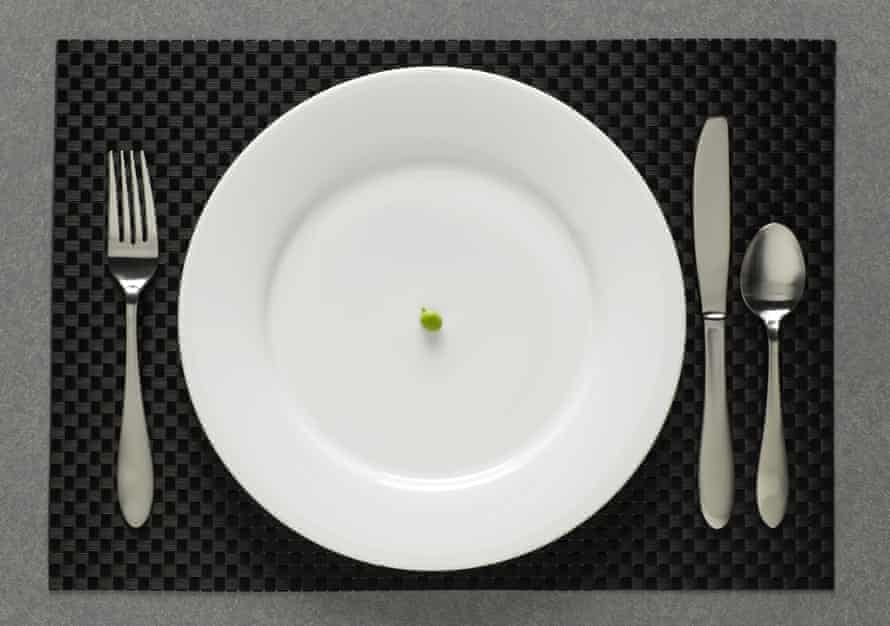 One green pea on a white plate