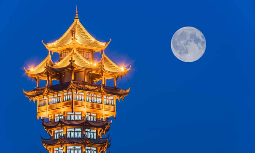 Jiutian Tower illuminated at night with full moon in the background, Chengdu, China.