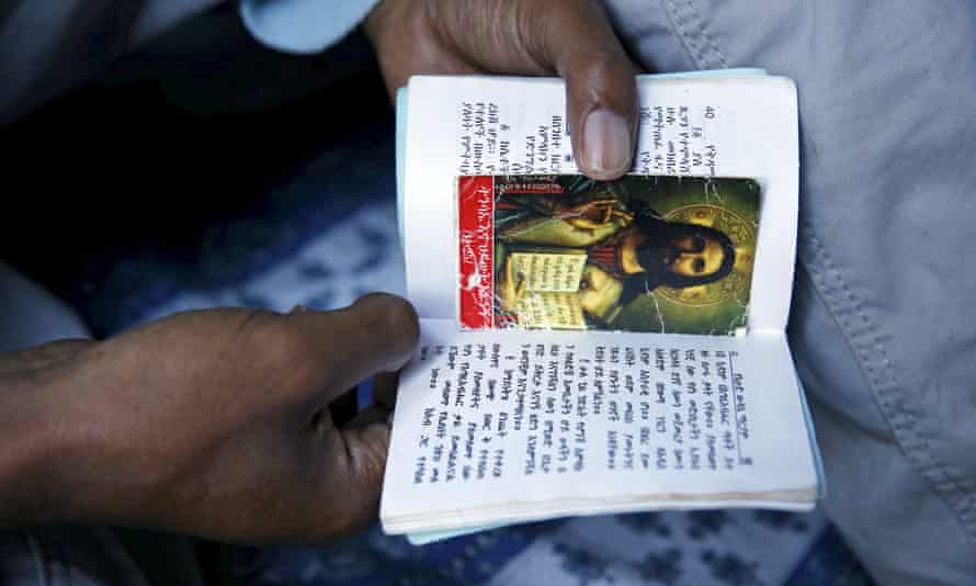 A Christian migrant from Eritrea prays and reads the bible