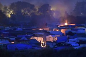 Migrants and refugees gather around a bonfire as they wait to be transferred to reception centres around France ahead of the Calais camp's demolition