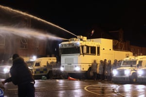 Objects are thrown towards PSNI officers and the water canon on Springfield Road