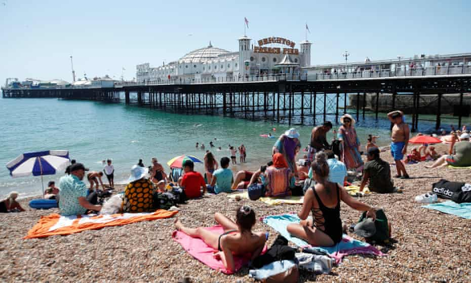 Beachgoers soak up the sun outside Brighton Palace Pier