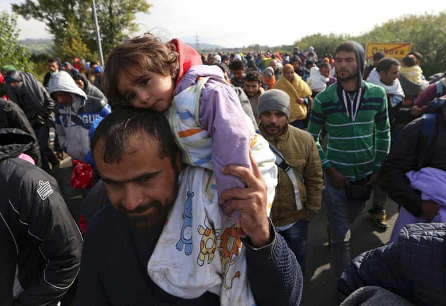 A migrant carries a child as they continue their journey in Dobova, Slovenia October 2015.