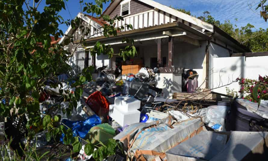 House surrounded by rubbish hoarded by owners