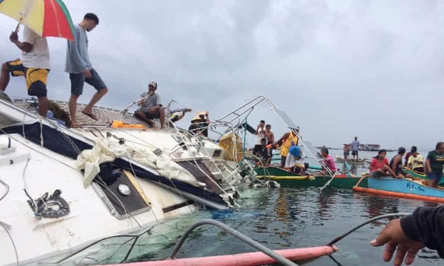 Filipino fishermen recovering the drifting yacht off Barobo town.