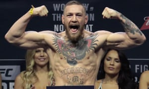 Conor McGregor stands on a scale during a weigh-in.