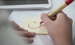 Close-up of woman at desk drawing a smiley face