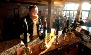 A man drinking a pint in a traditional english pub