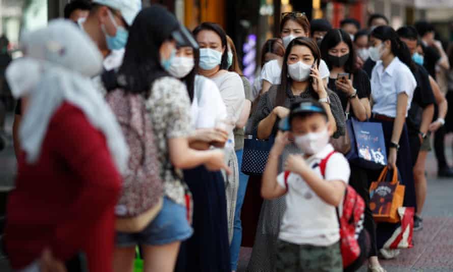 Chinese tourists buy protective masks at a supermarket in Bangkok