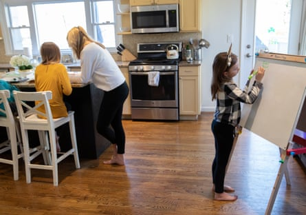 A mother assists her daughters with homeschooling in New Rochelle, New York.