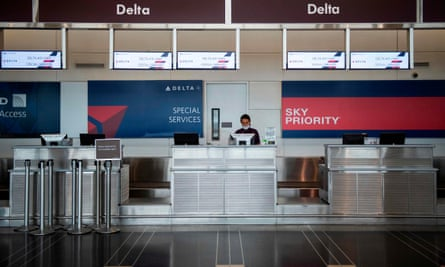 A Delta employee waits for passengers at Ronald Reagan Washington national airport. Twenty per cent of the company's workforce is taking voluntary retirements.