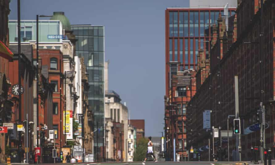 A woman walks across an empty Deansgate in central Manchester in late April.