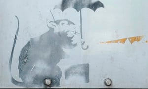 The small image of a rat holding an umbrella – possibly by Banksy – was found on a door designed to prevent flooding in a Tokyo monorail station.