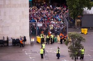 Fans queue to access the stadium.
