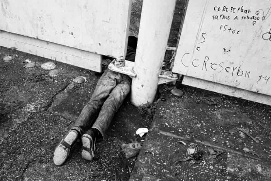 An unaccompanied minor tries to cross illegally under the gate at El Ceibo border