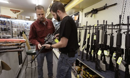 A sales representative shows a customer an an AR-15-style rifle.