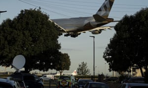 A police vehicle on patrol near Heathrow airport in London, as a plane comes in to land.