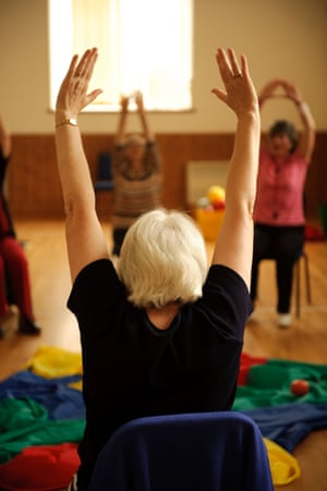 Older people taking part in low-impact chair aerobics in a village hall in Wales