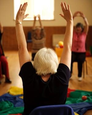 Women take part in a low-impact chair aerobics class