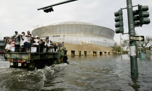 National Guard trucks haul residents through floodwaters to the Superdome.
