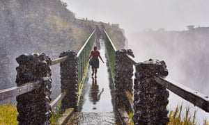 A visitor crosses a bridge at the Victoria Falls.