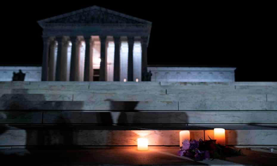 Flowers and candles are placed on the steps of the supreme court after the death of Justice Ruth Bader Ginsburg last year. Her replacement, Amy Coney Barrett, was one of five justices to allow the Texas law to stand.