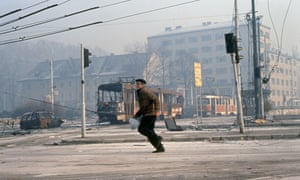 A civilian runs through the streets of Sarajevo, where Richard Holbrooke worked for the Clinton government