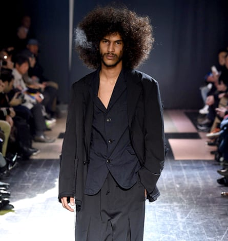 Man with an Afro, hand casually in pocket, in open-necked shirt, long-sleeved jacket and loose silky trousers