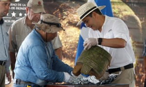 President Juan Orlando Hernández and an archaeologist unwrap an artifact piece during an official ceremony at El Aguacate air base in Catacamas<br>on Tuesday.