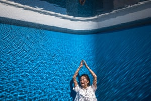 Beijing, China A woman poses for photos as she views the installation 'Swimming pool' during an exhibition of the work of Argentine conceptual artist Leandro Erlich at the CAFA Art Museum