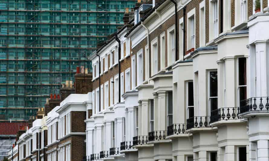 A row of terraced houses are seen below an apartment block in London