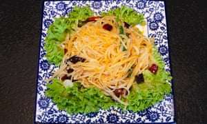A square blue floral plate with a dish of shredded potato, ringed with lettuce