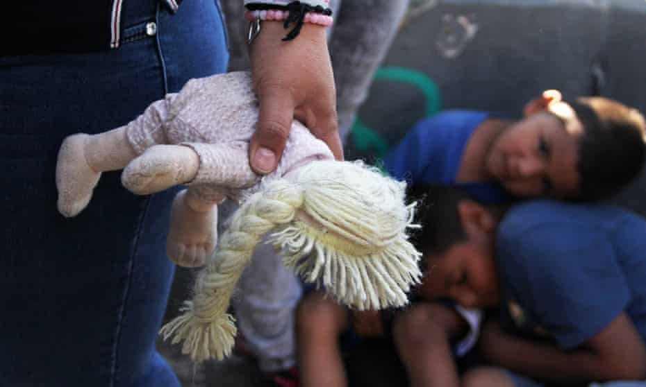 A Mexican woman holds a doll next to children at the Paso Del Norte port of entry at the US-Mexico border on 20 June 2018.