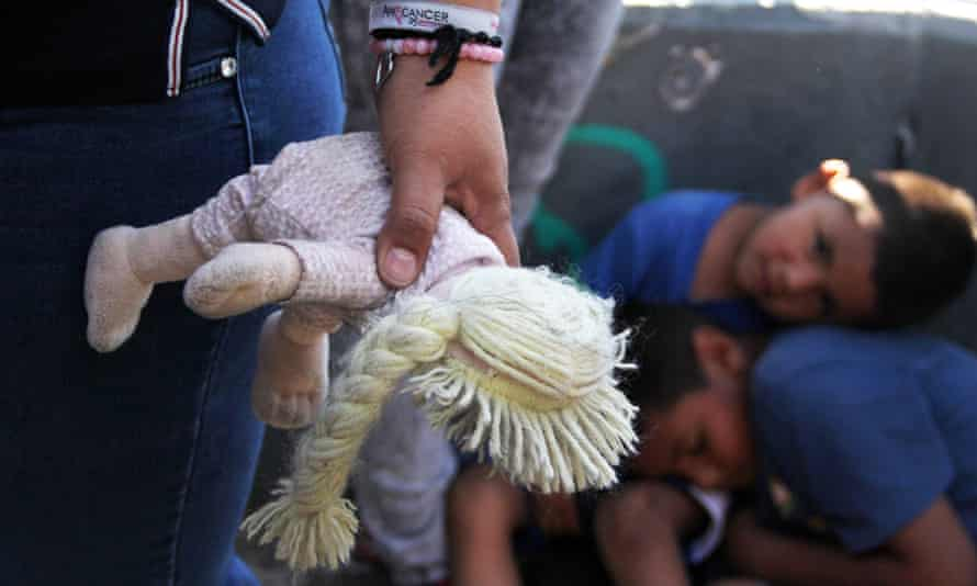 Mexican woman holds a doll next to children at the Paso Del Norte Port of Entry, in the US-Mexico border in Chihuahua state, mexico