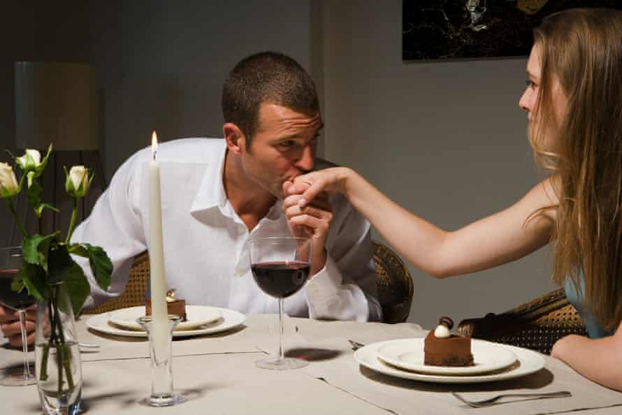 Man kissing back of woman's hand at candlelit dinner