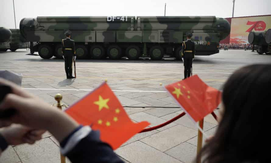 Chinese military vehicles carrying DF-41 ballistic missiles drive past flag-waving spectators during a parade in Beijing.