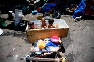 Children bathe in a makeshift tub in Manilla, the Philippines