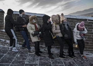 Tourists struggle to walk down an icy section of the Great Wall at Badaling, China