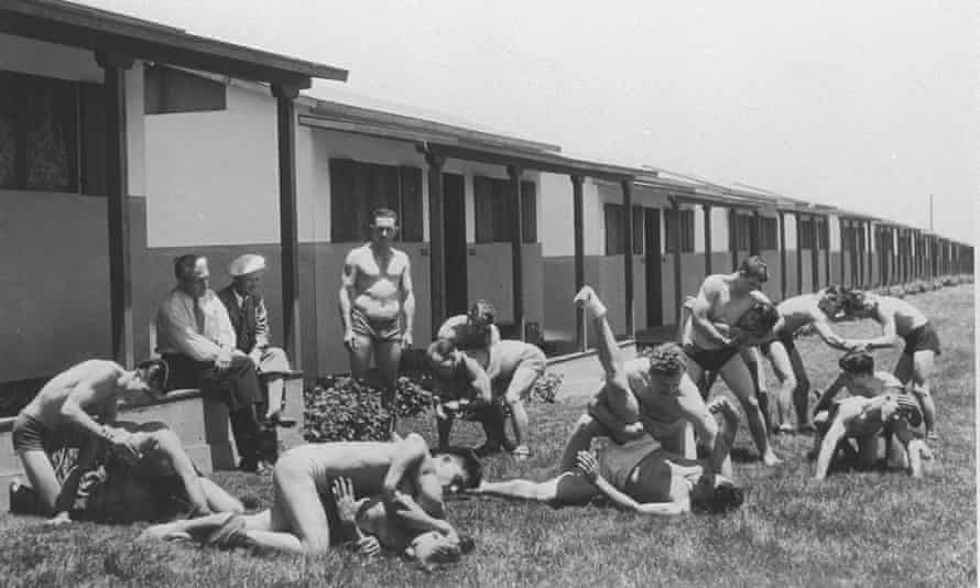 Black and white photo: a row of simple single storey huts – a lot like a 1950s UK holiday resort – in the sunshine 7 pairs of well muscled shirtless men wrestle together, while another shirtless man looks on, and two fully dressed men watch from the shade of a hut.