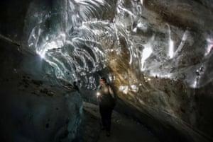 A tourist visits the Oktyabrskaya cave in the Bogdanovich glacier