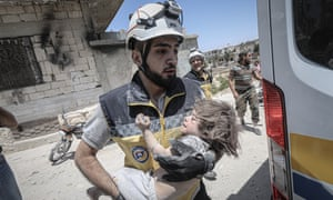 A rescue worker with a child saved from rubble in the Arihah district of Idlib after airstrikes by Russia and the Assad regime on 24 July.