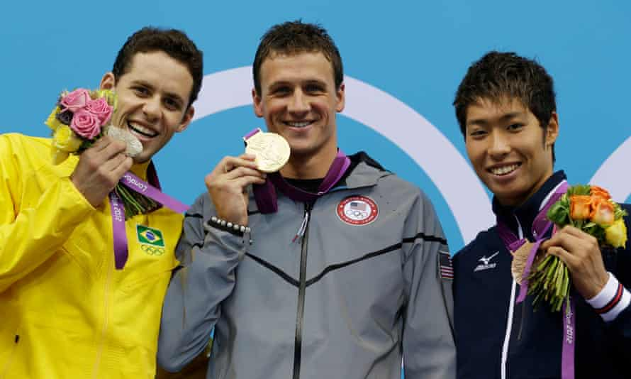 Ryan Lochte (centre) with one of his 12 medals during the 2012 Olympics.