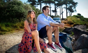 Sharon Horgan and Rob Delaney sitting on a rock, side by side, both staring straight ahead, in a scene from Catastrophe