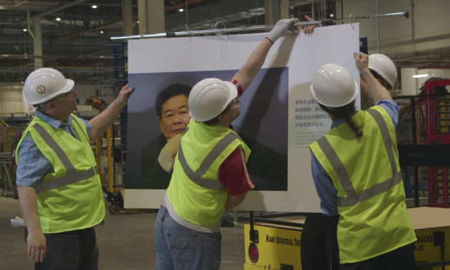 Workers at Fuyao Glass American, putting up photo of chairman Cao Dewang.