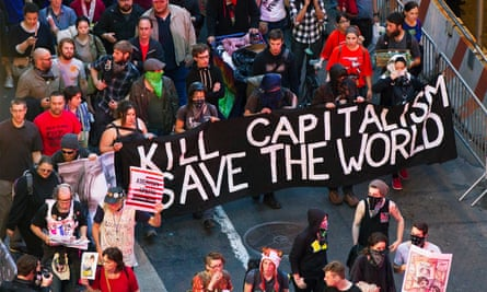 Members from the Occupy Wall Street movement carry signs as they march down Broadway during a May Day demonstration in New York