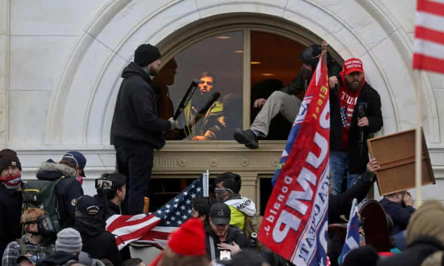 Trump supporters climb through a window they broke as they storm the Capitol building on 6 January.