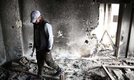 A rebel fighter walks in a flat destroyed by fire in a suburb of Damascus