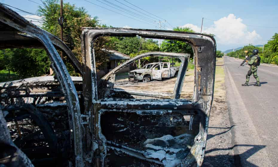 Police vehicles torched by gunmen who also killed 14 police officers in an ambush in El Aguaje village, in the municipality of Aguililla.