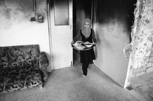 A young girl, Lama, serving food in her family's bomb-damaged home in Mosul, Iraq.